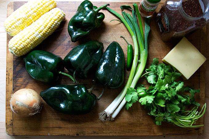 A board of ingredients: corn, poblanos, onion, scallions, cilantro, jalapeno, quinoa, and cheese.