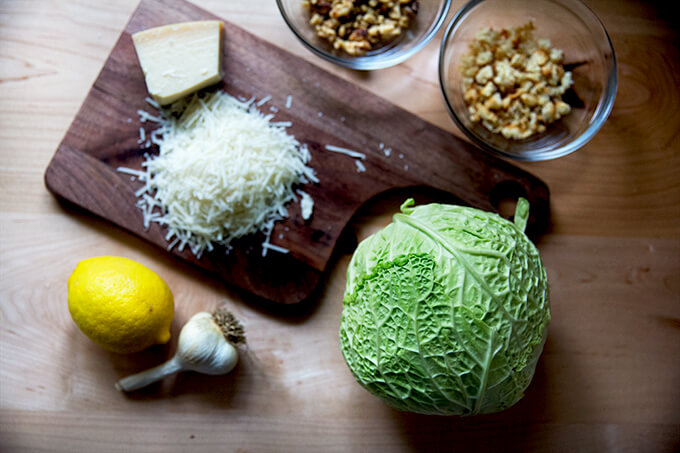 Roasted cabbage wedges ingredients on the counter: grated parmesan, cabbage, lemon, garlic, bread crumbs, walnuts.