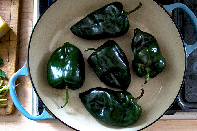 Poblanos being blistered in a skillet on the stovetop.