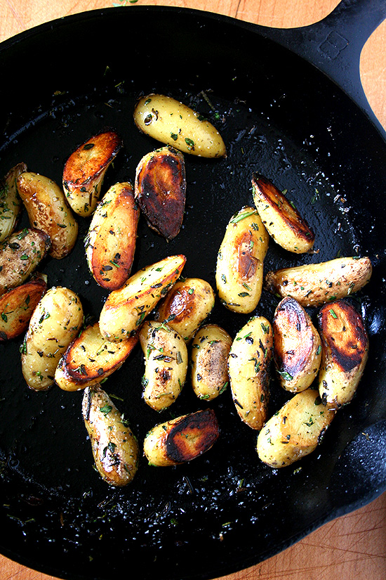 A cast iron skillet with crispy fingerling potatoes.
