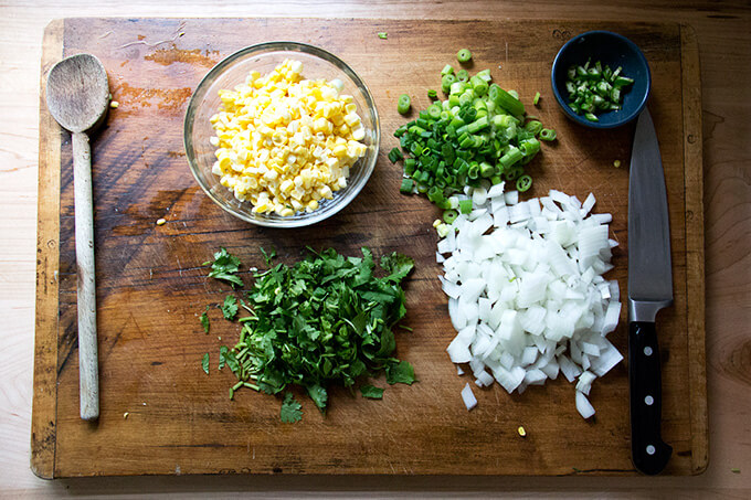 Prepped ingredients: chopped onions, scallions, herbs, chili and corn.
