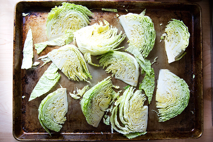A sheet pan with Savoy cabbage wedges on top.