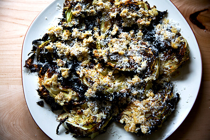 A platter of roasted cabbage wedges topped with walnut salsa and parmesan.
