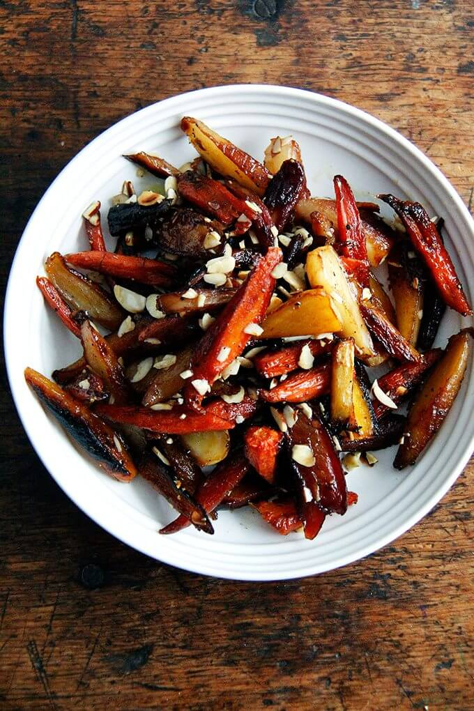 A bowl of twice-roasted carrots with honey and almonds.