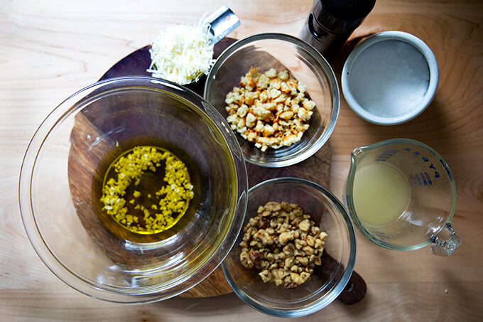 The ingredients for a walnut salsa: olive oil, minced garlic, parmesan, bread crumbs, walnuts, lemon, salt, and pepper.