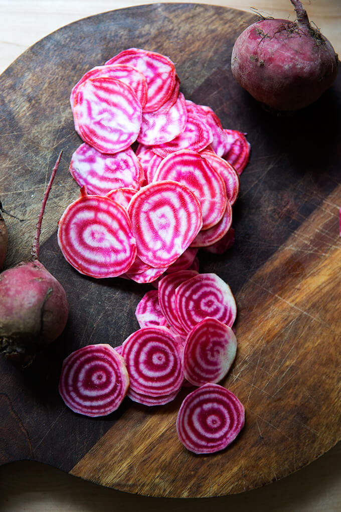 A board topped with thinly sliced candy striped beets.