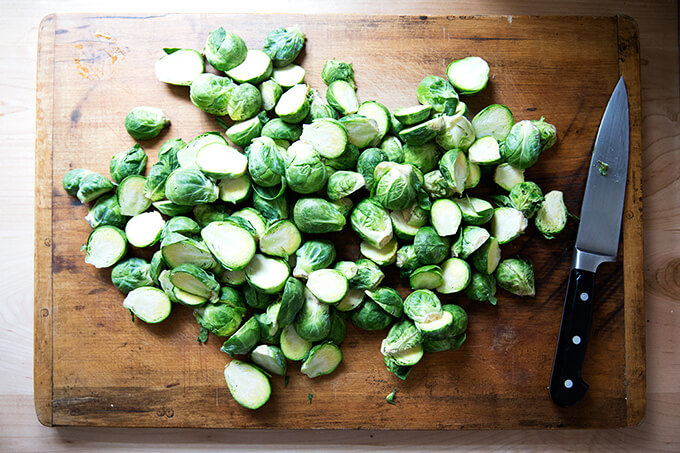 A board with halved Brussels sprouts.