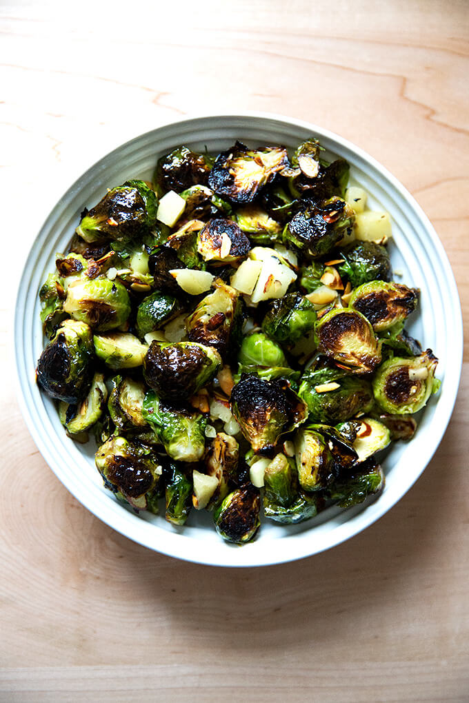 A bowl of roasted Brussels Sprouts with Almonds, Manchego, and balsamic.