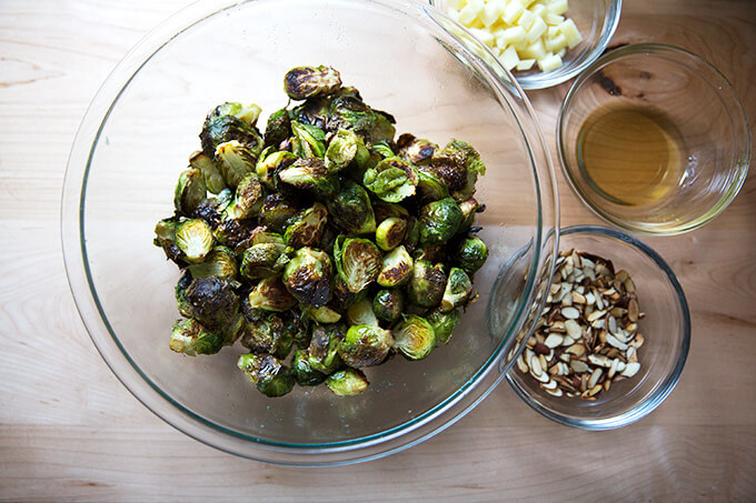 A bowl of roasted Brussels sprouts aside bowls of Manchego, almonds, and reduced balsamic.