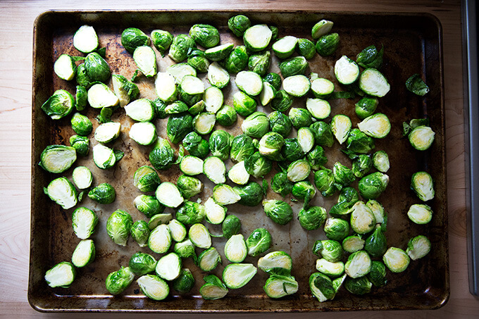 A sheet pan spread with halved Brussels sprouts, olive oil, and salt.