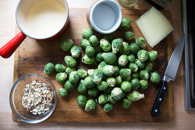 A cutting board with Brussels sprouts, almonds, salt, manchego, and vinegar.