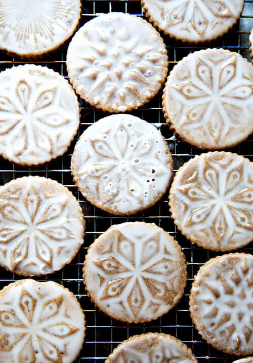 Stamped spiced brown butter muscovado cookies with maple glaze on a cooling rack.