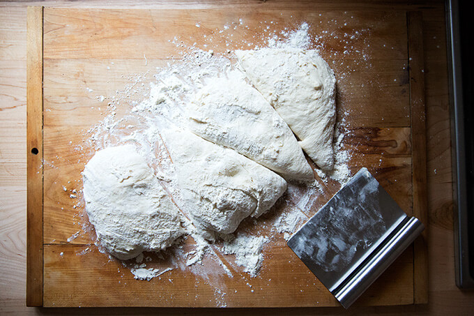 A floured work surface topped with homemade pizza dough, divided into 4 portions.