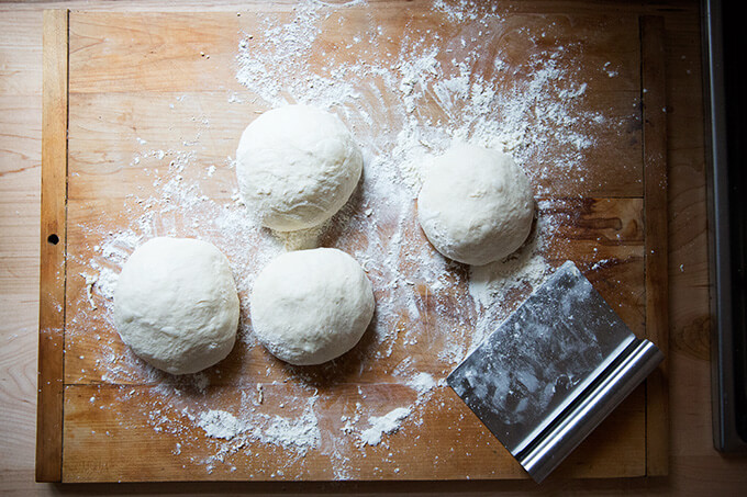 A floured work surface topped with 4 rounds of homemade pizza dough.