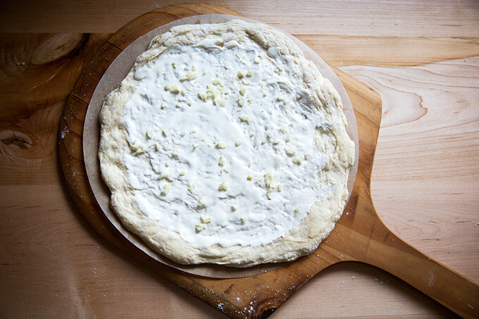 A round of pizza dough topped with creme fraiche and garlic.