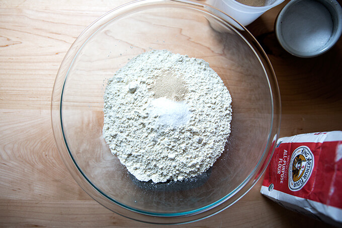 A bowl filled with flour, salt and yeast ready to make the simplest homemade pizza dough recipe ever.