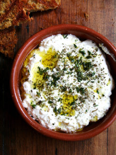 An overhead shot of a dish of whipped ricotta with olive oil, herbs and grilled bread.