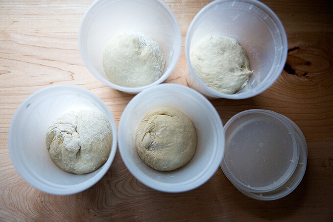 Four quart containers holding rounds of homemade pizza dough.