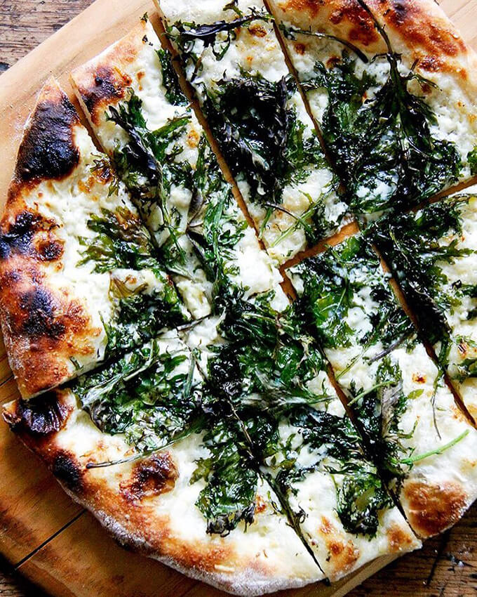 A homemade pizza dough recipe topped with kale and crème fraîche.