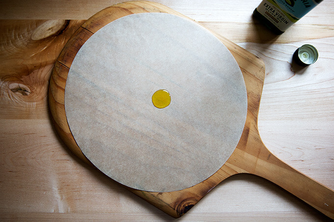olive oil on parchment on a pizza peel