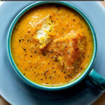 A bowl of carrot-ginger soup in a mug.