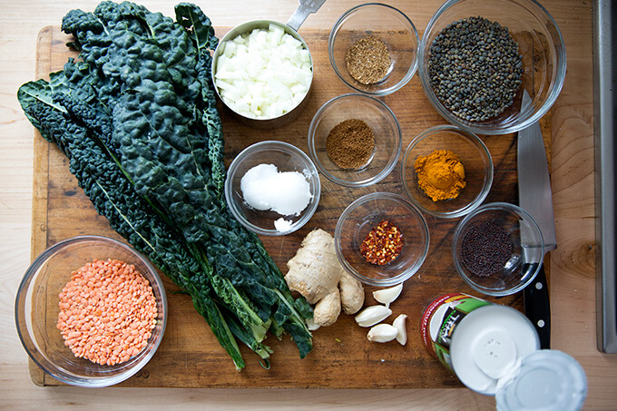 curried lentils with kale and coconut milk ingredients on a board.