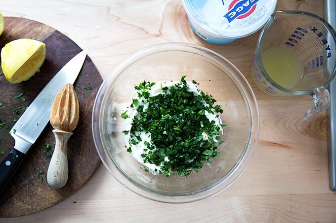 adding the parsley to the yogurt sauce