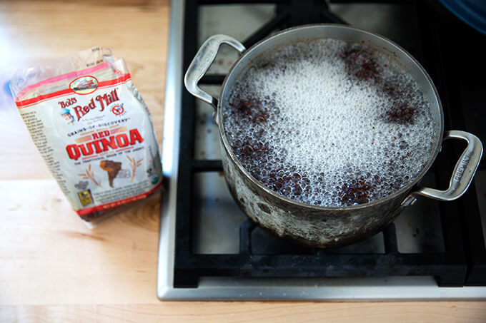 red quinoa boiling in a pot