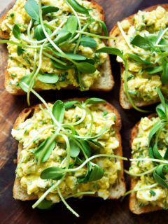 Four slices of toasted sourdough bread topped with avocado-egg salad and sprouts.