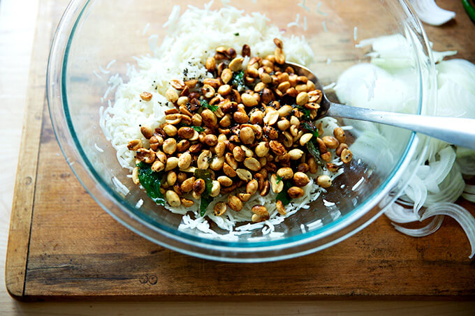 A bowl of rice, lime, peanuts and curry leaves.