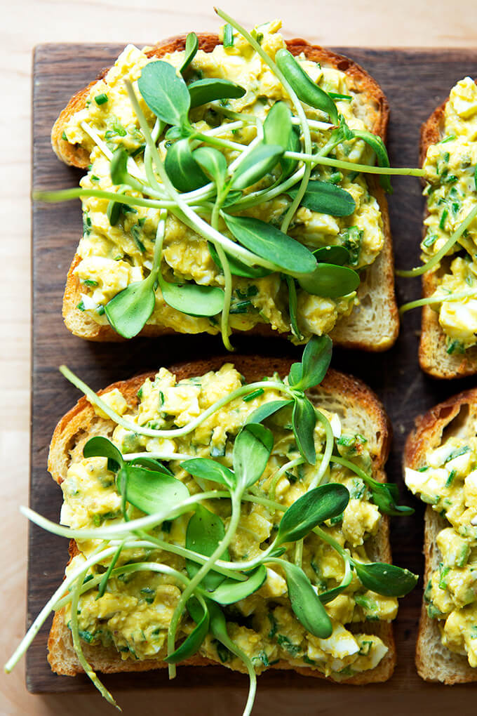 Slices of toasted sourdough bread topped with avocado-egg salad and sprouts.