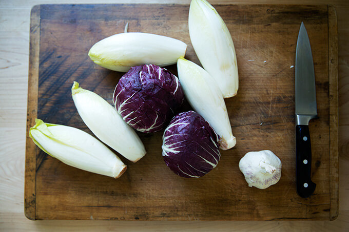 Belgian Endive, radicchio, and garlic on a cutting board.