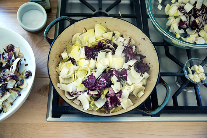 A sauté pan with olive oil, garlic, endive and radicchio.