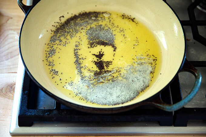 A braiser pan with ghee and mustard seed.