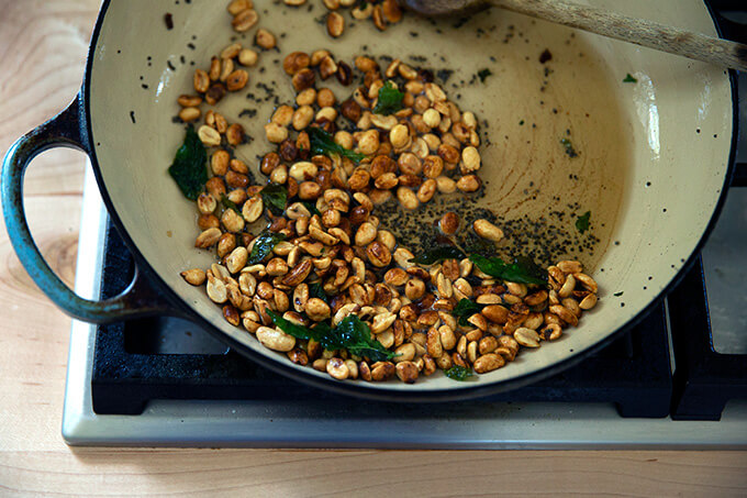 A braiser pan with ghee, mustard seed, curry leaves, and peanuts.
