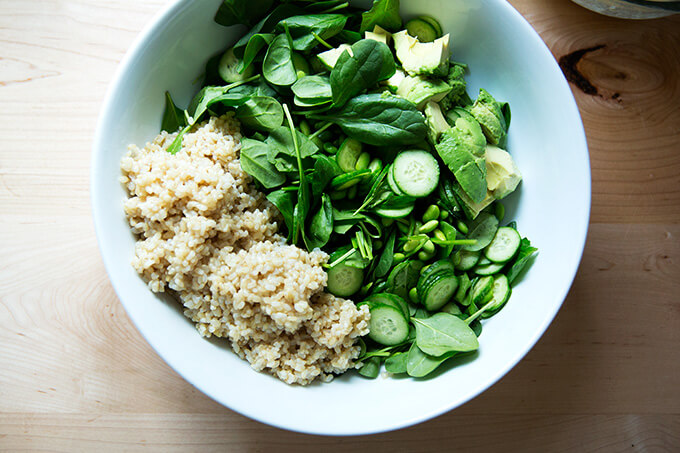 A bowl of brown rice, spinach, edamame, cucumber, and avocado.