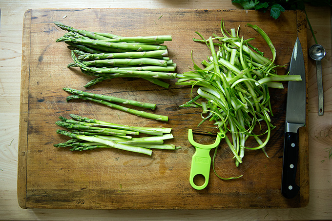A cutting board with asparagus, shaved with a peeler.
