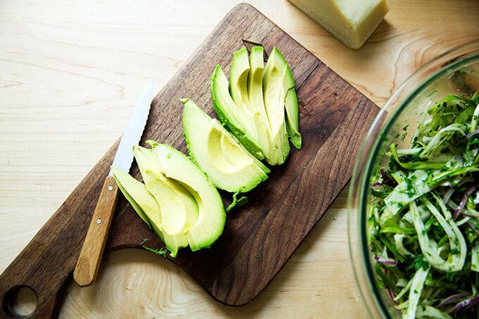 A cutting board with avocado, sliced for fennel salad.