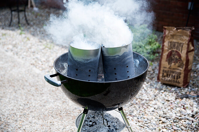 A weber grill filled with two smoking chimney starters.