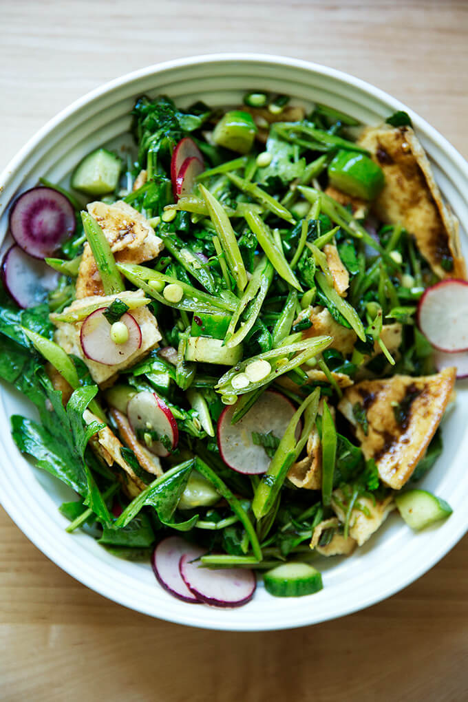 A bowl filled with a spring fattoush salad with arugula, radishes, snap peas, and cucumbers.