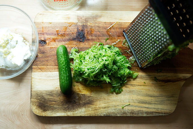 A cutting board with grated cucumber.
