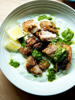 A platter of grilled, smokey chicken, cucumber-yogurt sauce,, skhug and lemon