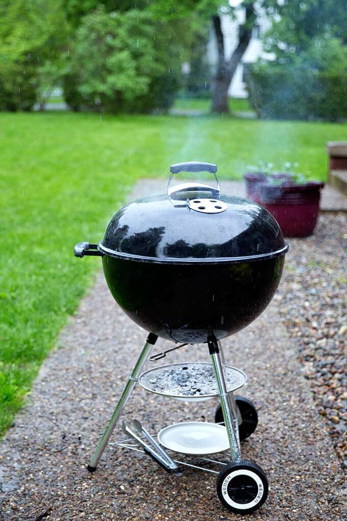 A weber grill with hot coals in the rain.