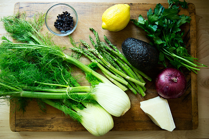 A cutting board holding the ingredients for the shaved fennel salad: fennel, asparagus, onion, lemon, parsley, parm, and currants.