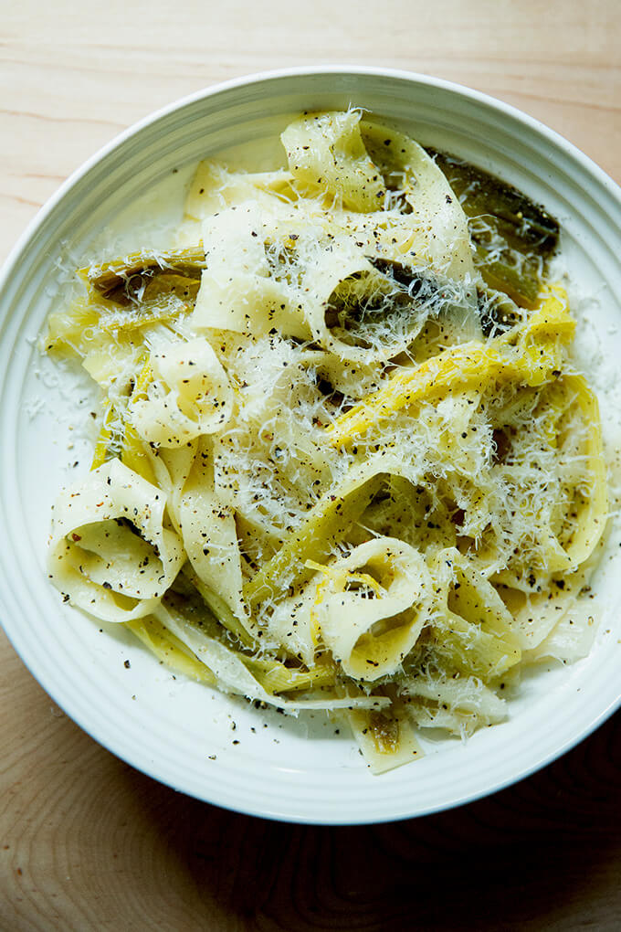 A bowl of braised leek pappardelle with grated parmesan over top.