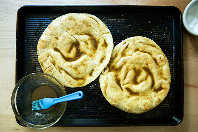 A sheet pan holding two rounds of pita brushed with oil, cumin and salt.