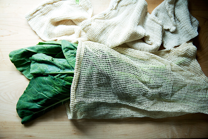 A reusable produce bag filled with collard greens.