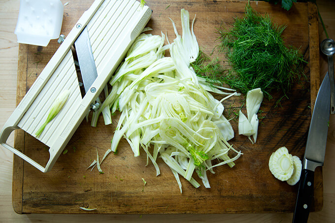 Cutting board with shaved, raw fennel and a Benriner mandoline.
