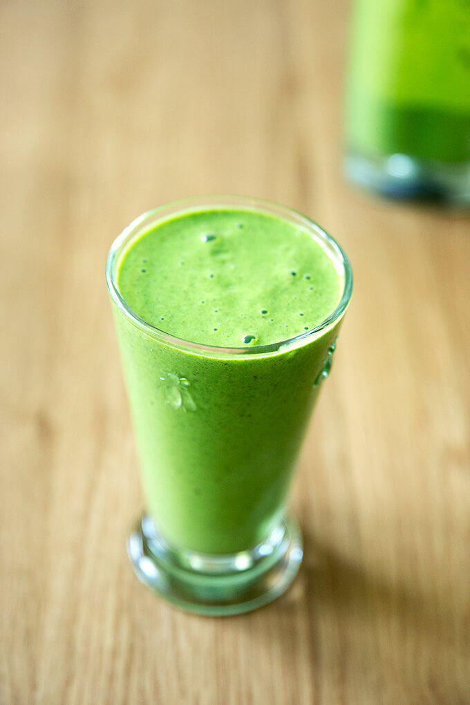 A tall glass filled with a green smoothie.