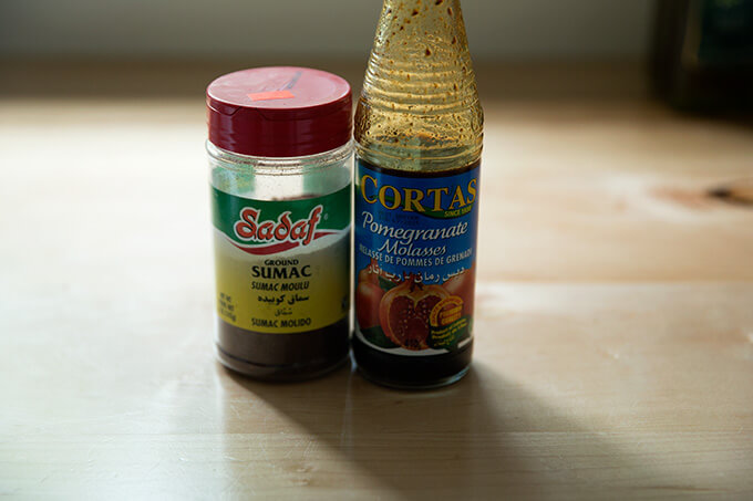 A jar of sumac and a bottle of pomegranate molasses sitting on the counter.